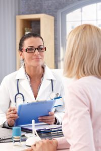 28345385 - happy female brunette doctor with glasses at medical office with patient, smiling, clipboard in hand, wearing stethoscope and lab coat.