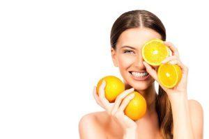 43906352 - joyful young woman holding juicy oranges before her eyes