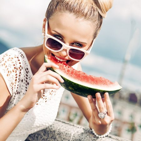 30739767 - beautiful young girl with bow tie hair in white summer dress wearing sunglasses bites juicy watermelon