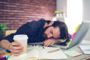 45537740 - tired creative editor holding disposable cup while sleeping on office desk