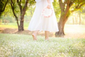 70420206 - soft focus woman walking in the field with flower crown