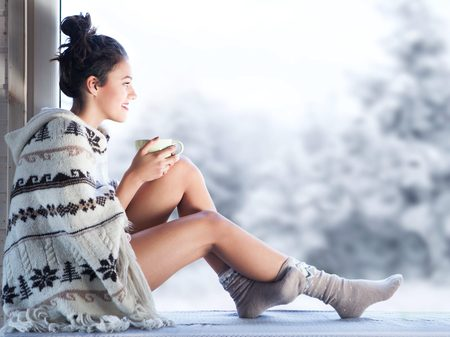49400407 - young beautiful brunette woman drinking cup of coffee wearing knitted nordic print poncho sitting home by the window. blurred winter snow tree background